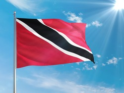Trinidad And Tobago national flag waving in the wind against deep blue sky. High quality fabric. International relations concept.