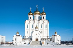 Trinity christian orthodox cathedral in Magadan, Russia, white church with golden domes on sunny winter day with clear blue sky