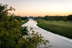 Trinity River Fort Worth, Texas. Sunset over the water, orange and golden colors. Green grass and trees in a public park. Peaceful and calm summer evening. Horizontal orientation.