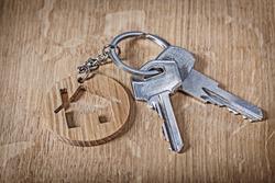 trinket house and keys on wood background