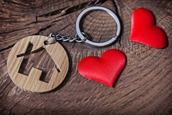 trinket house without  keys on wood background and heart toys