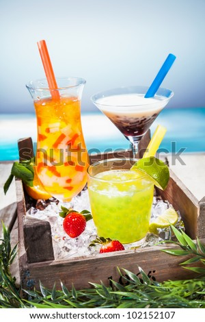 Trio of colourful tropical cocktails blended with fruit in different shaped glasses served overlooking a tropical beach