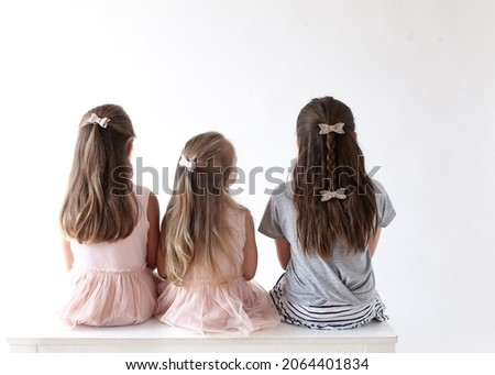 Trio of friends sitting from behind on a white bench
