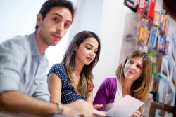Trio of students sitting in a classroom working together in a collaborative atmosphere