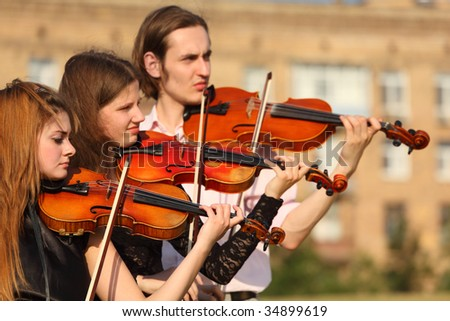 trio of violinists plays outdoor - stock photo