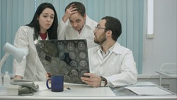 trio of young afraid physicians checking patient's head scanning