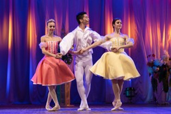 Trio of young girls ballerinas and a young man dancing ballet performance on stage in the theater on a blue purple background