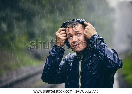 Trip in bad weather. Portrait of young man in drenched jacket in heavy rain.