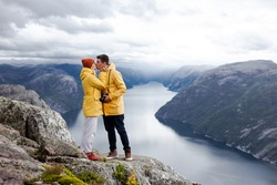 Trip to Norway. Couple of tourists in yellow raincoats with camera are kissing on the Preikestolen (Preacher's Pulpit or Pulpit Rock) with view on Lysefjord in cloudy summer day