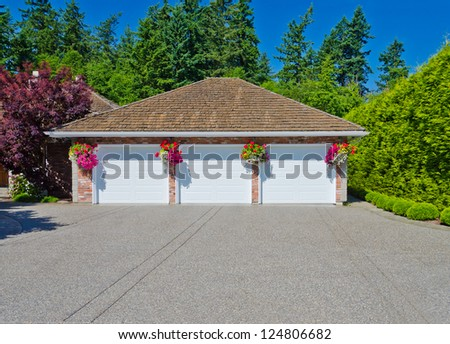 Triple doors garage with hanging flower pots. Vancouver, Canada. - stock photo