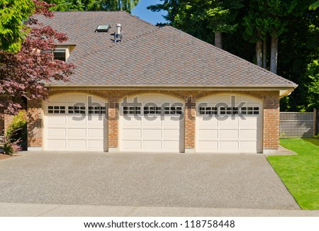 Triple doors garage with wide long driveway.