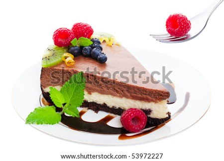 Triple layer, chocolate cheesecake served on a chocolate drizzled plate and garnished with raspberries, blueberries, kiwi, and fresh lemon balm.  Delicate citrus curls add a touch of elegance.