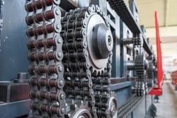 Triple strand roller chain going around three sprockets on industrial machine
