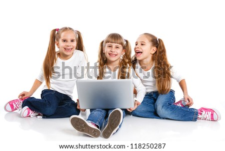 Triplets with notebook. Three attractive sisters using a laptop. Isolated on white background