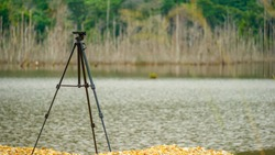 Tripod kept near a lake side without camera. isolated tripod in nature