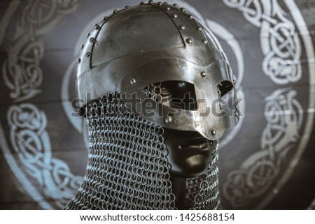 Triskel, Vikings, viking helmet with chain mail on a red shield with golden shapes of sun, weapons for war #1425688154
