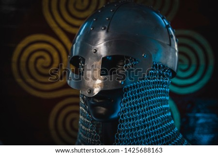 Triskel, Vikings, viking helmet with chain mail on a red shield with golden shapes of sun, weapons for war #1425688163