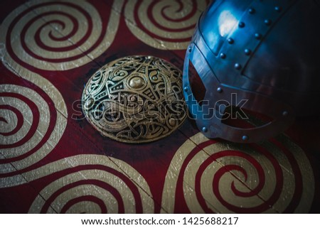 Triskel, Vikings, viking helmet with chain mail on a red shield with golden shapes of sun, weapons for war #1425688217
