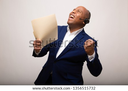 Triumphant African American Businessman Holds Up File