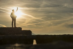 Triumphant businessman greeting a new day standing outdoors on a wall with his fist raised against a sun with copy space.