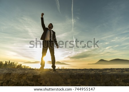 Triumphant businessman greeting a new day standing outdoors with his fist raised against a fiery sunrise with a sunburst between his legs and copy space.