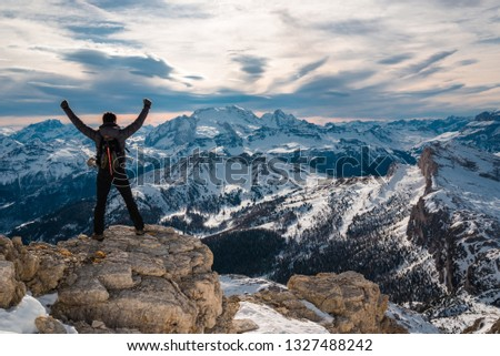 Triumphant man conquer the summit standing in front of beautiful landscape