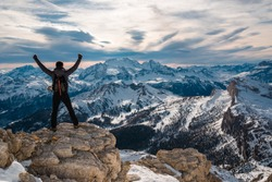 Triumphant man conquer the summit standing in snowy beautiful landscape with arms up, Cortina Italy holiday destination. Beautiful place icon, iconic mountain panorama and winter vacation places
