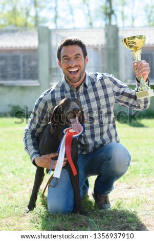 triumphant man holding trophy with dog wearing rosette