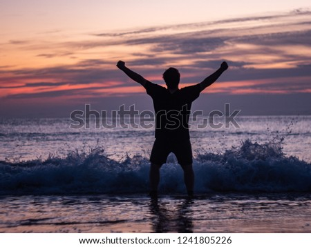 Triumphant man in front of the rough sea during a setting sun