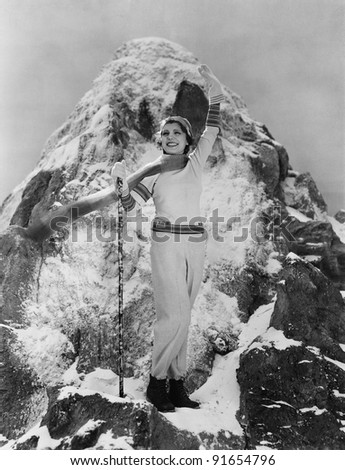 Triumphant woman at mountain summit - stock photo