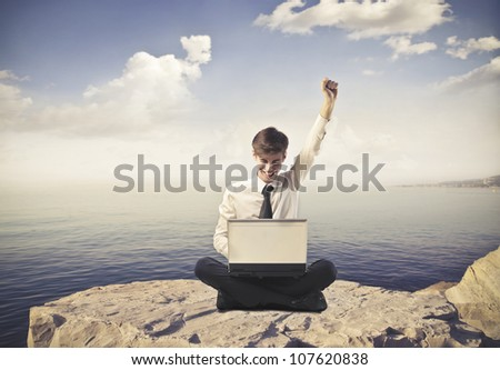 Triumphing young businessman in front of a laptop with seascape in the background - stock photo