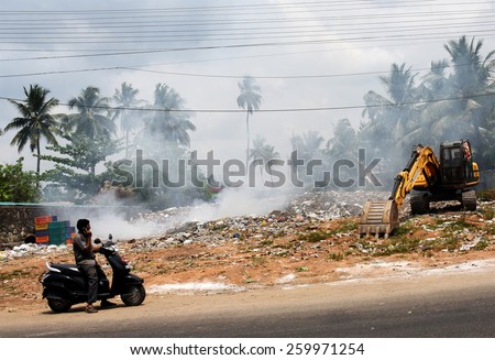 TRIVANDRUM, KERALA, INDIA, MARCH 04, 2015: Land and air pollution in India. Environmental hazard. Garbage being burnt in the open, a health hazard. A man on scooter stops to talk on his mobile phone.