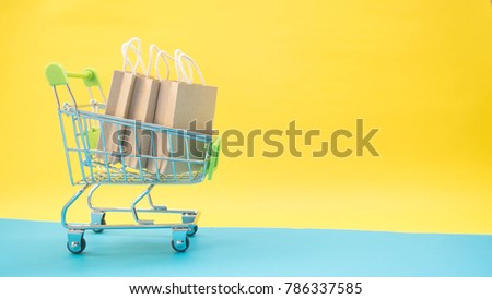 Trolley cart and brown recycle paper shopping bags on yellow blue background. Creative idea for shopping online, summer sale, supermarket concept. Minimal style. Copy space.