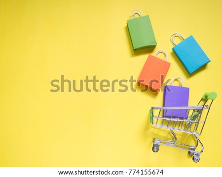 Trolley cart and colorful paper shopping bags on yellow background. Creative idea for shopping online, summer sale, supermarket, discount promotion and Black Friday concept. Copy space for text.