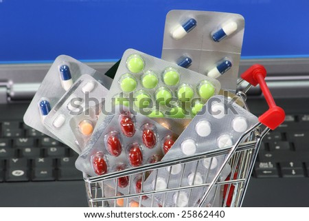 Trolley filled with pills labtop iin background
