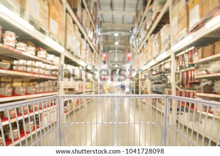 Trolley Shopping Cart Between Kitchenware Shelf Section in Supermarket  Warehouse Retail Outlet as Modern Lifestyle Shopping Concept with bokeh. #1041728098
