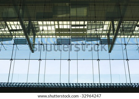 trolleys lined up against the large window panel at the airport
