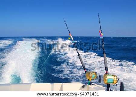 Trolling fishing boat rod and golden saltwater reels deep blue ocean sea wake