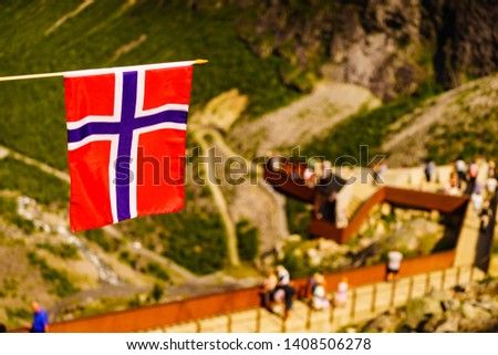 Trollstigen mountain road landscape in Norway, Europe. Norwegian flag waving and many tourists people on viewing platform in background. National tourist route. #1408506278