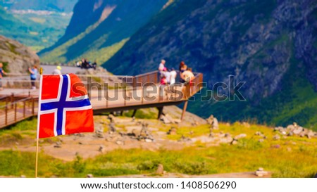 Trollstigen mountain road landscape in Norway, Europe. Norwegian flag waving and many tourists people on viewing platform in background. National tourist route. #1408506290