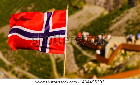 Trollstigen mountain road landscape in Norway, Europe. Norwegian flag waving and many tourists people on viewing platform in background. National tourist route. #1434455303