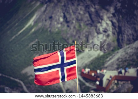 Trollstigen mountain road landscape in Norway, Europe. Norwegian flag waving and many tourists people on viewing platform in background. National tourist route. #1445883683