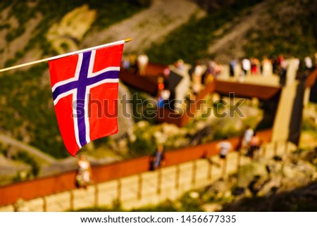 Trollstigen mountain road landscape in Norway, Europe. Norwegian flag waving and many tourists people on viewing platform in background. National tourist route. #1456677335