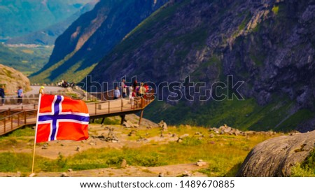 Trollstigen mountain road landscape in Norway, Europe. Norwegian flag waving and many tourists people on viewing platform in background. National tourist route. #1489670885