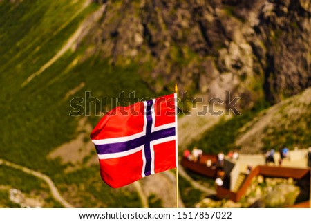 Trollstigen mountain road landscape in Norway, Europe. Norwegian flag waving and many tourists people on viewing platform in background. National tourist route.