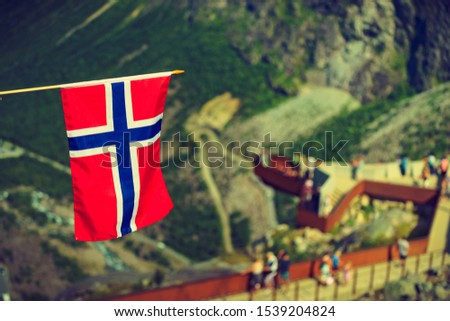 Trollstigen mountain road landscape in Norway, Europe. Norwegian flag waving and many tourists people on viewing platform in background. National tourist route. #1539204824
