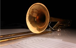 Trombone and sheet music on a glossy white table