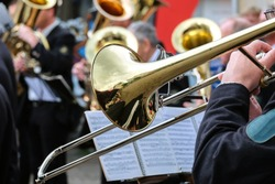 Trombone choir gives concert in the open air – close up of the front trumpet player with selective focus
