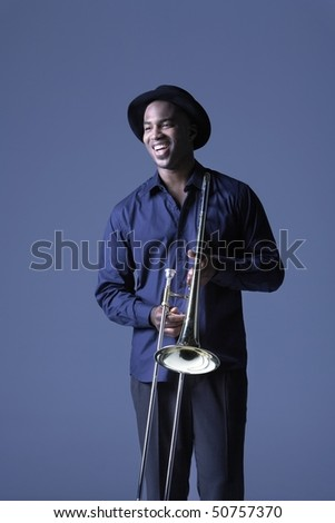 Trombone Player standing with hat, smiling - stock photo