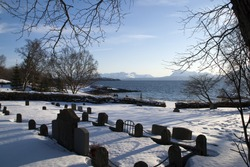 Trondenes Norway, graveyard at 13th century medieval church with bay in background